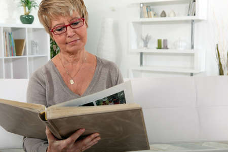grandmother skimming through family album in lounge photo