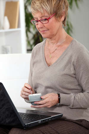 surfing the internet: Senior woman at home with laptop