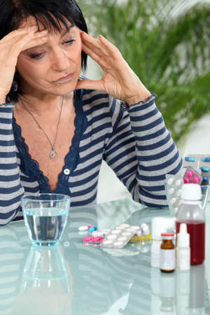 medicate: Woman with headache taking her medication