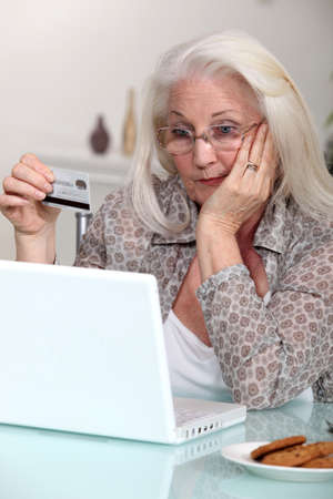 Old woman with credit card and computer photo