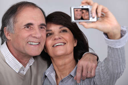 Middle aged couple taking a picture of themselves photo