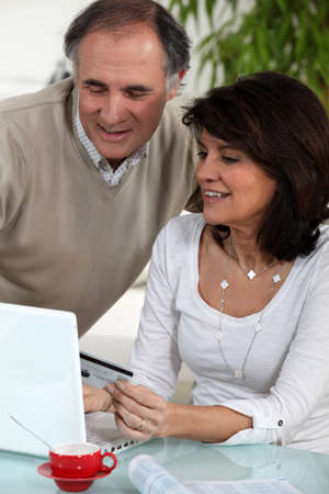 Middle-aged couple doing some on-line shopping photo