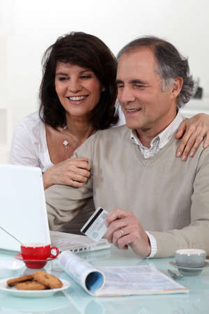 enjoying life: Middle-aged couple sat at computer with credit-card