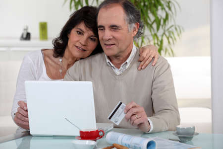Middle-aged couple shopping on-line photo