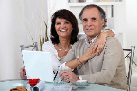 Mature couple using a credit card online photo