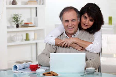 A middle age couple looking at a laptop. photo