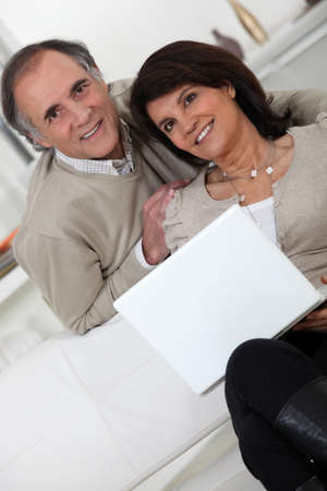Married couple sat on the sofa with laptop Stock Photo - 14203878