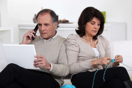 Man on phone and woman knitting at home photo