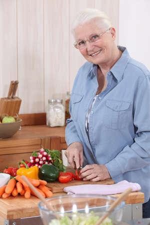 Elderly lady preparing vegetables photo