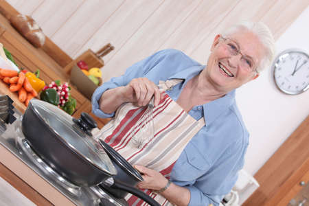 Old lady cooking in kitchen photo