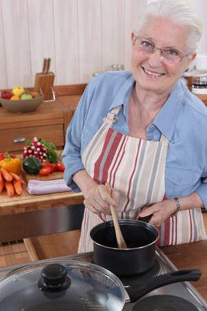 abuela: Anciana cocina en su cocina Foto de archivo