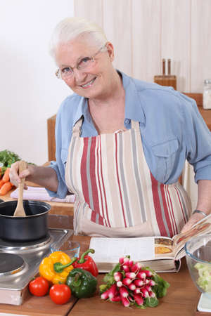 Elderly woman cooking with the help of a recipe photo