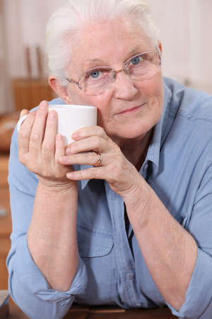 wise woman: Old lady drinking from mug Stock Photo