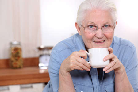 Elderly lady enjoying cup of tea in her kitchen photo