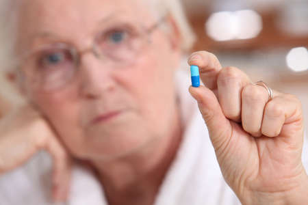 Elderly woman holding a capsule between her fingers Stock Photo - 14204503