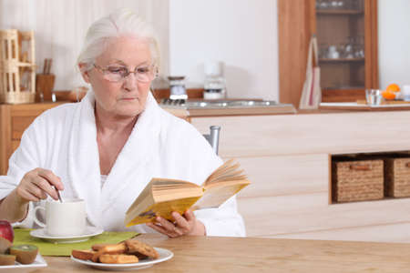 Elderly lady reading over breakfast photo