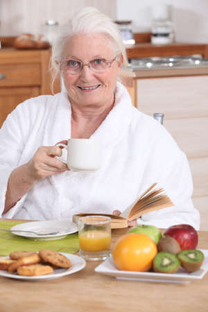 Senior woman having a relaxed breakfast photo