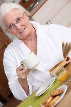 Elderly woman having breakfast photo