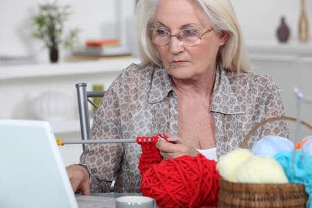 Elderly woman knitting photo