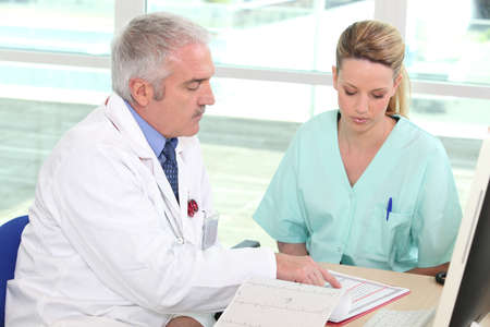 residents: General practitioner and caregiver sitting at a table Stock Photo