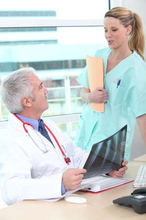 nurse clipboard: Doctor having a conversation with his assistant Stock Photo