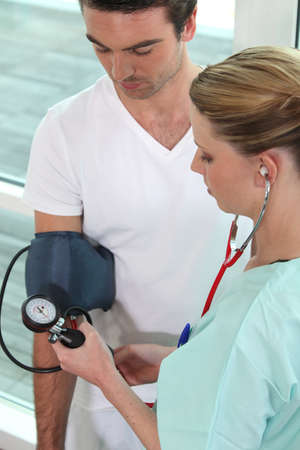 Young nurse taking blood pressure of a man photo