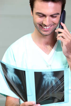 electromagnetic radiation: Doctor examining some x-rays while talking on the phone Stock Photo