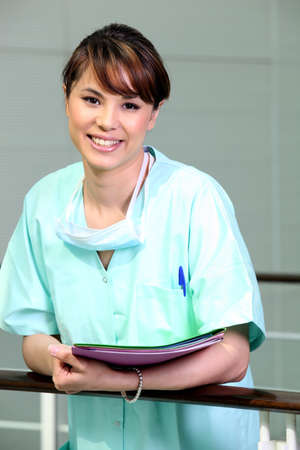 clinical staff: Nurse in scrubs holding files Stock Photo
