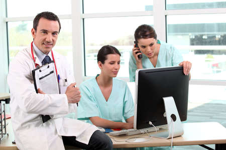 Three doctors gathered around desk Stock Photo - 14207431