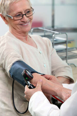 a nurse taking blood pressure of a smiling senior woman photo