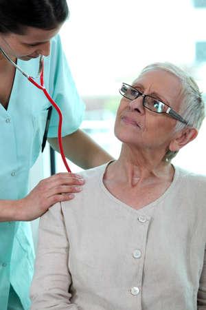 Nurse taking patients heart rate photo