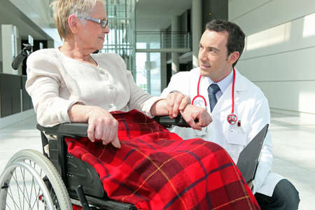 Doctor talking to a woman in a wheelchair photo