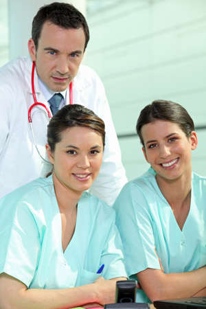 Doctor standing with two nurses at a nursing station photo