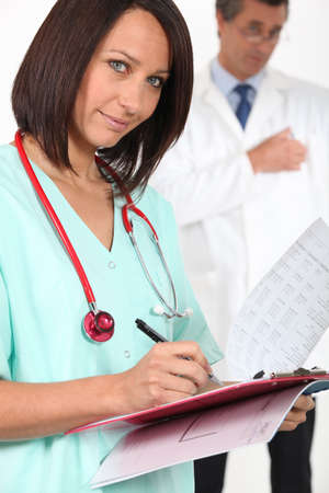 Medical professional filling in a patient record photo