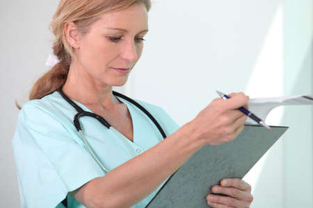Blond female nurse holding clipboard