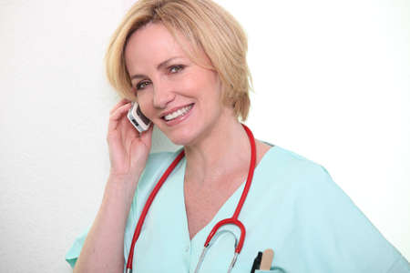 trained nurse: Female nurse speaking on mobile telephone