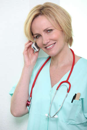 ear phones: Medical professional talking on her mobile phone Stock Photo