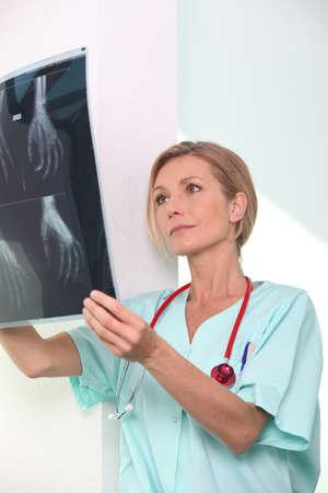 Female nurse examining x-ray print Stock Photo - 14206542