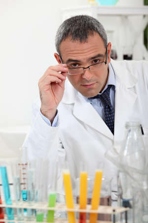 capable of learning: scientist touching his glasses behind test tubes in a laboratory