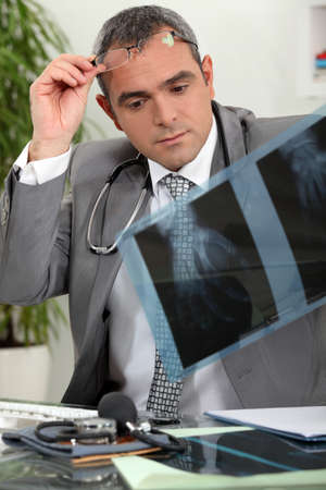 greying: Doctor looking at x-rays