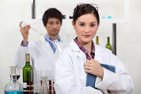 Man and woman testing wine in laboratory photo