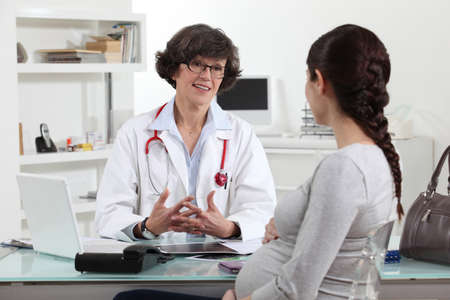 consultant physicians: Pregnant woman in doctors appointment Stock Photo
