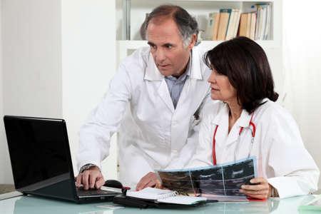 Two doctors examining x-ray photo
