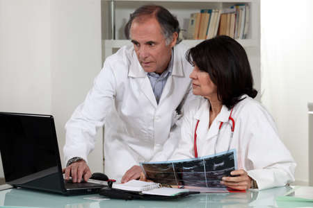 Doctors looking at laptop screen photo