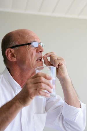 personas tomando agua: Senior hombre de tomar su medicina Foto de archivo
