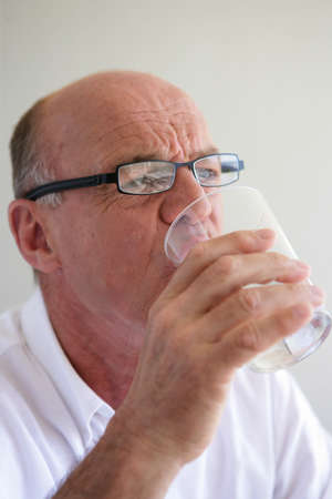 Elderly man drinking a glass of water photo