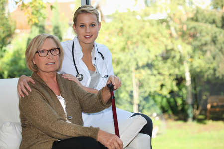 Elderly woman and young female caregiver at home photo