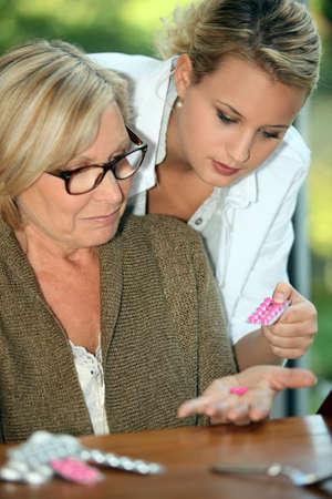 약물 치료: 그녀의 할머니의 약을주는 젊은 여자 스톡 사진