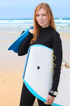 wetsuit: Young female surfer with bodyboard and flippers