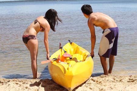 women bathing: Young couple dragging their kayak onto the lake Stock Photo